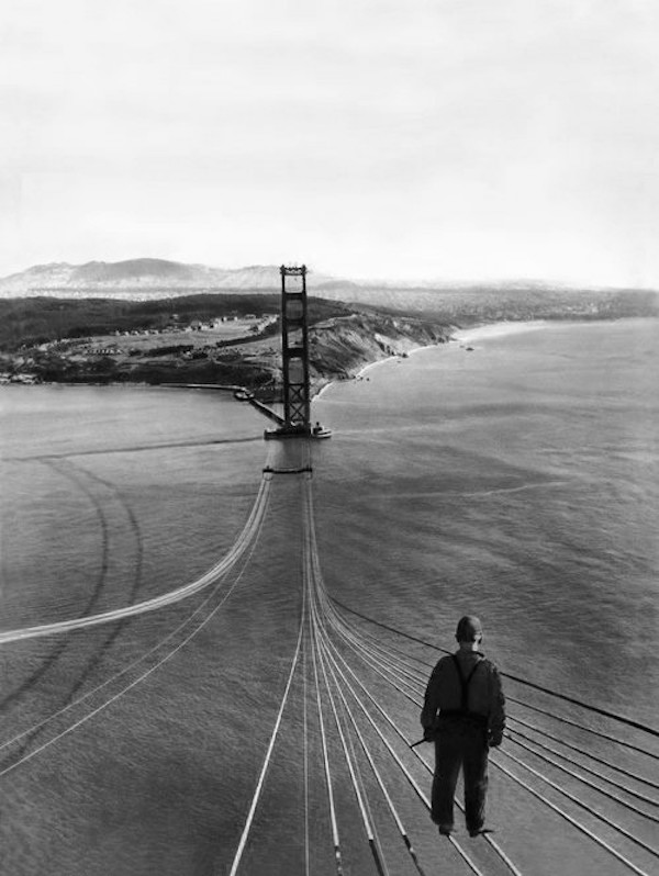 A man stands on cables over the Golden Gate Bridge, circa 1933.