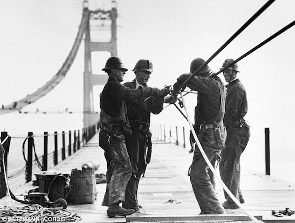 The bridge was built between 1933 and 1937, with men shown here working on the cables in 1935.
